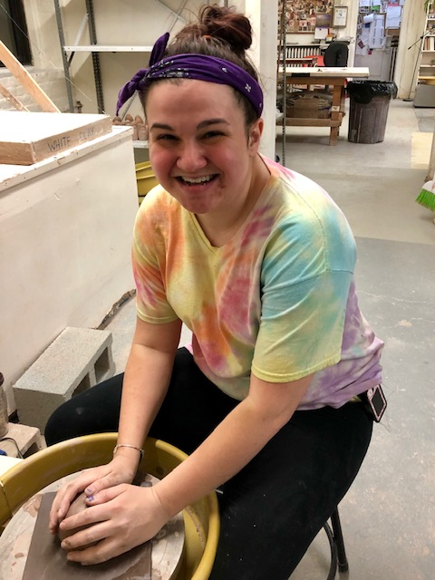 Mindy sitting at a pottery wheel